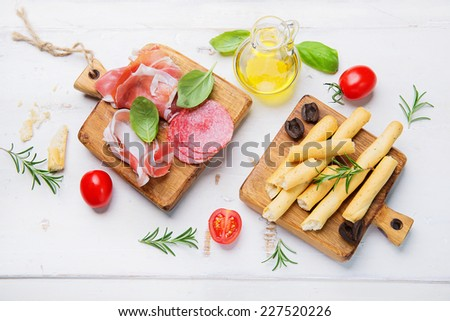 Cold meat plate and grissini bread sticks on wooden background - stock photo