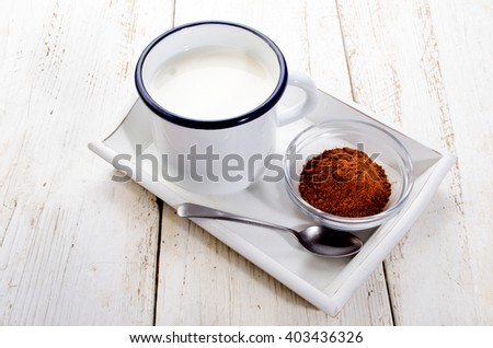 cold milk in a enamel cup, cocoa in small glass bowl on serving tray - stock photo