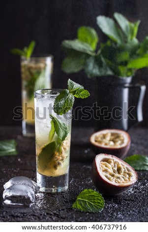 Cold mojito with passion fruit, mint and ice on the black background - stock photo