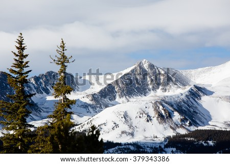 Cold Mountain Peak - This is an image of a snowy mountain peak shot with an out of focus pine trees in the foreground. Shot with a shallow depth of field. - stock photo