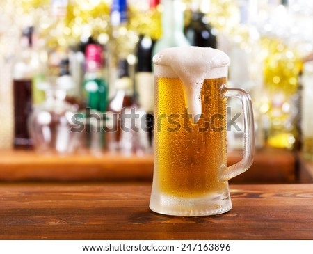 cold mug of beer in bar - stock photo