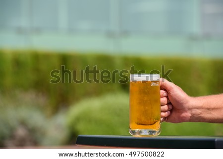 cold mug of fresh beer in hand