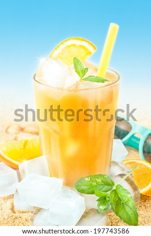 Cold orange juice in a tall glass with mint leaves and ice cubes on sand background - beach bar summer holiday beverages menu. - stock photo