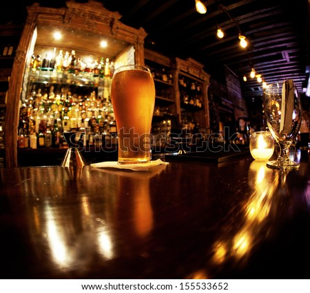 Cold pint of beer sitting on a bar - stock photo