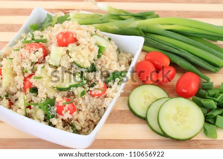 Cold quinoa salad with cucumbers, cherry tomatoes, green onions and herbs - stock photo