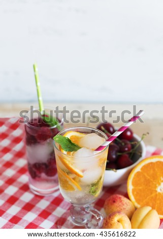 Cold refreshing cocktail with fresh orange, raspberry and mint.  - stock photo