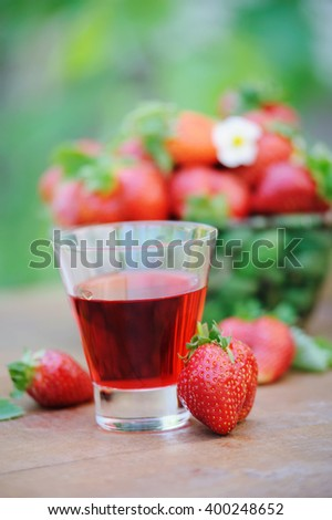 Cold refreshing drink from strawberrie sand ripe berries in basket on wooden table outdoor