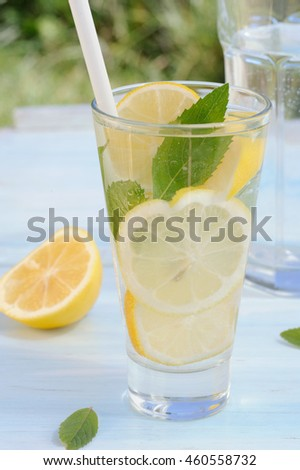 Cold refreshing water with fresh lemons and mint in glass on blue rustic table