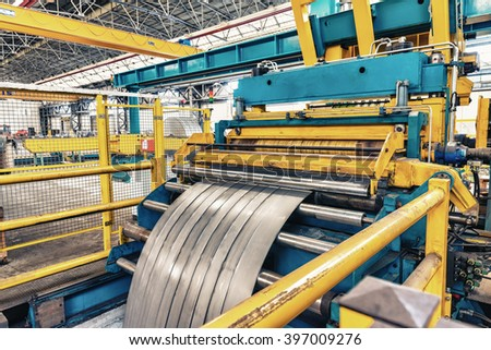 Cold rolled steel coil on decoiler of machine in metalwork manufacturing.