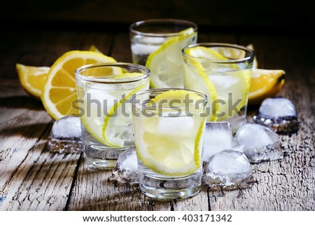 Cold Russian vodka with lemon and ice in shot glass, vintage wooden background, selective focus - stock photo