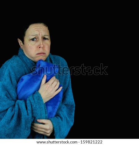 Cold, shivering woman holding hot water bottle. Dressed in bathrobe. Isolated against black background. - stock photo