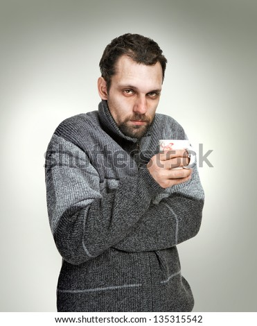 Cold, sick man dressed in grey sweater holding a cup of tea in hands isolated on grey background looking at the camera - stock photo