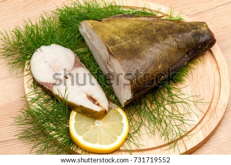 Cold smoked fish and a slice of lemon on a kitchen board