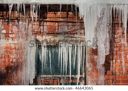 Cold snow winter frozen ice melting icicle on wall - stock photo