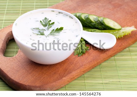 cold soup with avocado, cucumber and yogurt on a wooden board, top view
