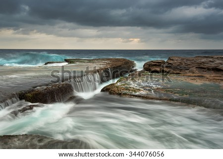 Cold stormy seascape with rushing wave and flowing water