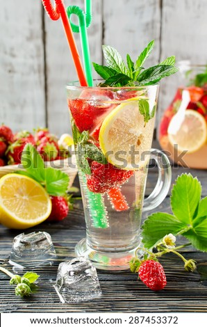 Cold summer drink with mint, strawberry and lemon - stock photo