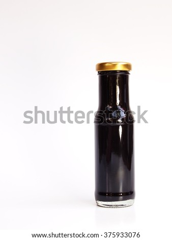 cold sweet juicy healthy dark red brown color mulberry juice full filled in small size clear glass bottle with golden colour cap ready for drink on white paper background