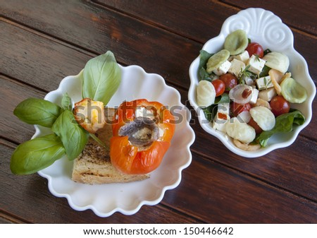 Cold tasty appetizer, with goat and lamb cheese stuffed red pepper, served on grilled olive bread, Macaroni salad with feta cheese, cherry tomatoes and Mediterranean herbs, selective focus - stock photo