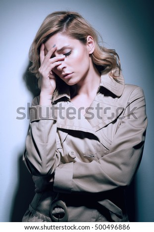 Cold toned portrait of a sad or tired blonde woman suffering a headache, holding her face with a hand, standing near a wall. Blonde girl with curly hair in beige coat. Pain, illness, depression.
