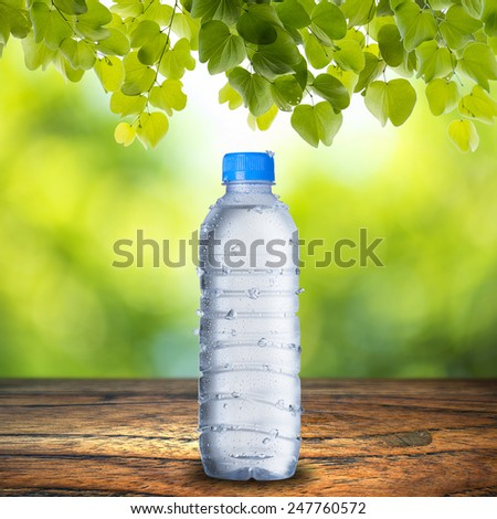 Cold Water Bottle and Glass Of Ice Cubes on Wood Table With Light Bokeh Background - stock photo