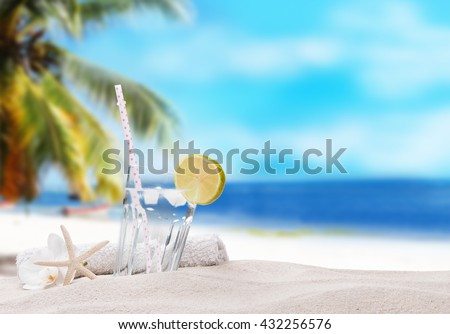 Cold water drink with ice and a slice of lime on sand with tropical beach background