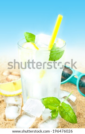 Cold water in a tall glass with lemon, mint leaves and ice cubes on sand background - beach bar summer holiday cold beverages menu. Layout with free text space. - stock photo