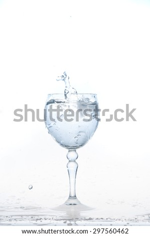 cold water splash on a glass on white background, Ice cubes splashing into glass of water
