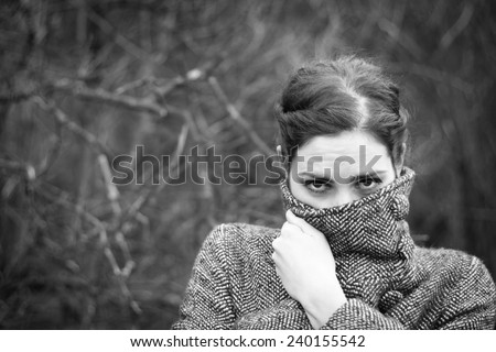 Cold weather: young woman wrapping up in her coat - stock photo
