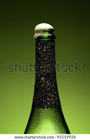Cold wet bottle of champagne with Froth