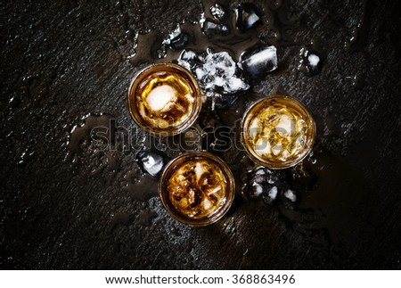 Cold whiskey in a glass with crushed ice on a black stone wet background, top view - stock photo