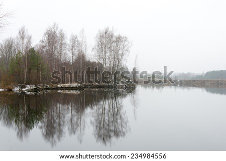 cold winter landscape with frozen river and icy water