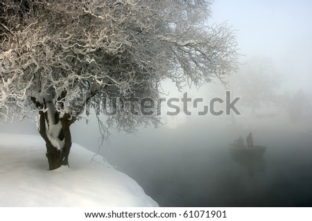 Cold winter morning by the river, with rising fog and wooden rowboat.