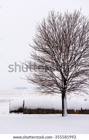 Cold WInter Snow on Bales of Hay with a Farm Field - stock photo