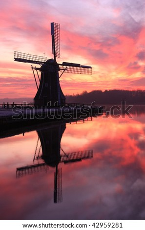 Cold winter sunset and Dutch windmill reflected in a lake. - stock photo