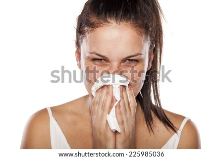 cold woman snorts in a napkin - stock photo