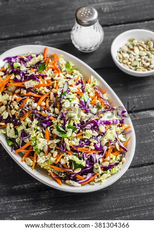 Cole slaw with seeds and pine nuts - delicious healthy vegetarian food. On a dark rustic wooden background