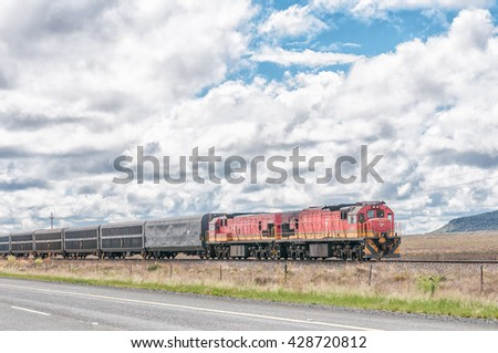 COLESBERG, SOUTH AFRICA - MARCH 8, 2016: Two diesel-electric locomotives pulling a train through typical Karoo landscape between Noupoort and Colesberg in the Northern Cape Province