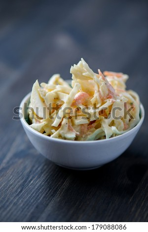 Coleslaw in a bowl on a wooden table - stock photo
