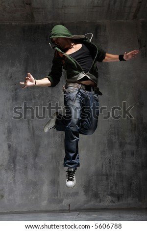coll looking dancer posing on a grunge grey wall - stock photo
