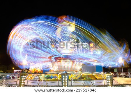 COLLADO VILLABA, SPAIN - JULY, 27: Long eposure picture of a carrusel rotating during the local fair in a small amusement park in Collado Villaba, Spain, on July 27, 2014. - stock photo