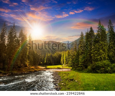 collage landscape with pine trees in mountains and a river in front flowing to lake in sunset light with rainbow - stock photo