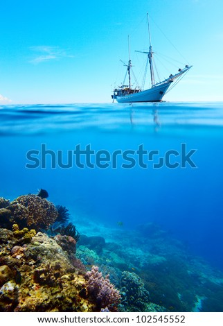 Collage of a coral reef and anchored sail boat on a surface - stock photo