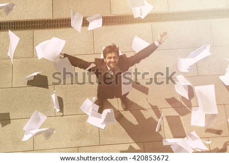 Collage of businessman or freelance man on street with his arms raised. Many sheets of paper are around him. Office building, Top view. Toned. - stock photo
