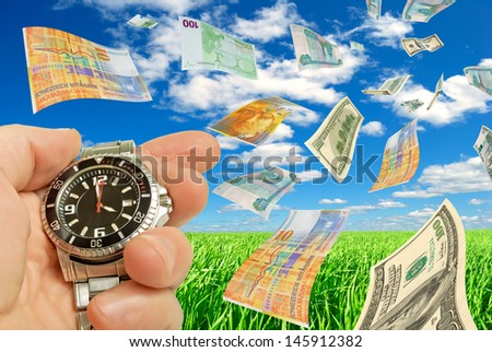 Collage with currency and a clock in a hand on a background of sky and grass. - stock photo