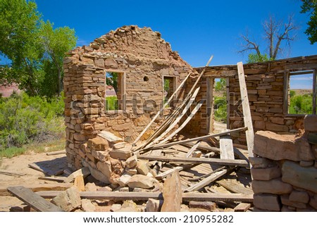 Collapsed wooden roof lies on the floor of a stone house in the wilds of southern Utah. - stock photo