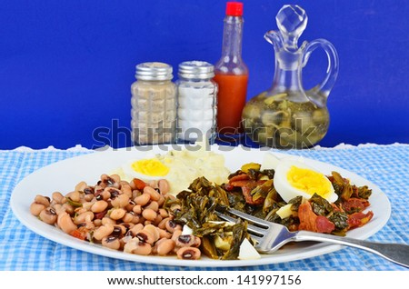 Collard greens seasoned with bacon drippings and salt pork and garnished with boiled egg on white plate with potato salad and black eyed peas.  Blue gingham setting adds to Southern or Soul Food Feel. - stock photo