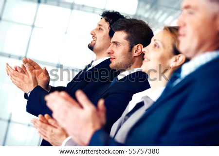 Colleagues applauding during a business meeting in the office.