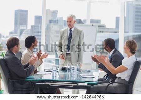 Colleagues applauding the boss during a meeting in the meeting room - stock photo