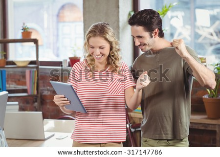Colleagues cheering while looking at digital tablet at office